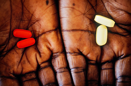 A pair of hands holding a pill in each. Photo: Panos.