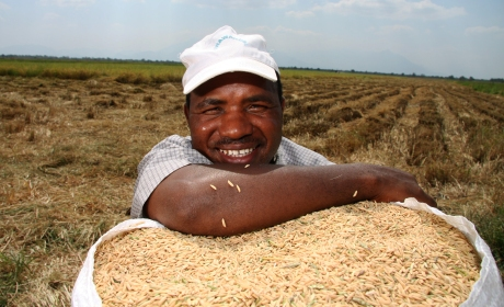 Emanuel Mahendi is photographed in Morogoro, Tanzania, with a sack of rice. Tanzania's ranking in the HDI improved one place in the HDR 2014.