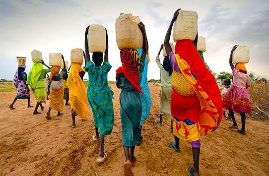 Woman carrying water collected from taps installed by international aid agencies in a camp for internally displaced persons. They fled their homes after being attacked by militias.