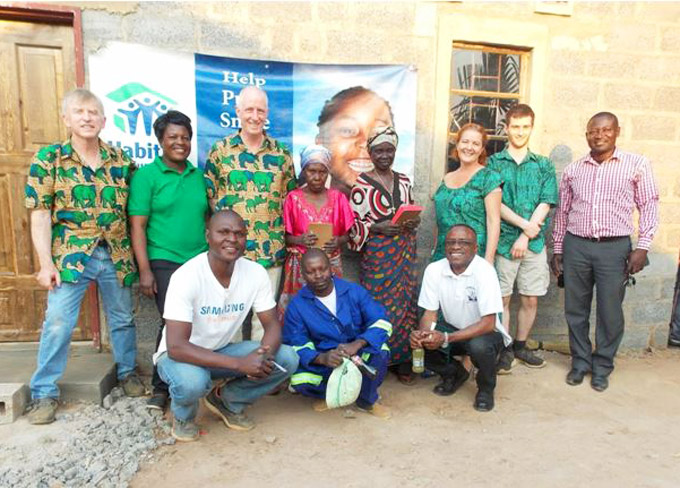 Michael Nugent stands with new Habitat homeowners Failet and Jennifer, local Habitat for Humanity builders and staff, and his teammates, outside one of the two newly built homes in Chipulukusu, Zambia in 2016. © Michael Nugent