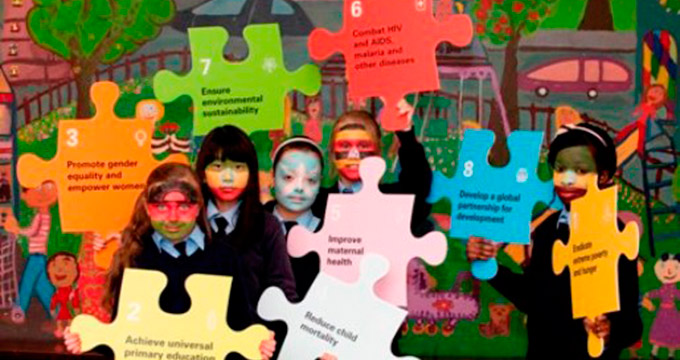 Primary school students holding a Millenium Development Goal-related jigsaw puzzle